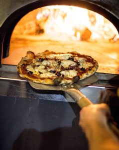 Wood fired pizza coming out of the oven. Ready to eat.