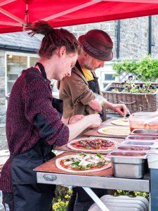 Sarah and Dan preparing pizza at their mobile pizza oven